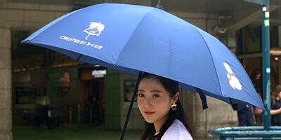 青空の下、傘を差して爽やかに移動するイメージ